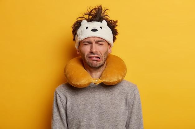 Passageiro do sexo masculino usa travesseiro de viagem para dormir durante a viagem