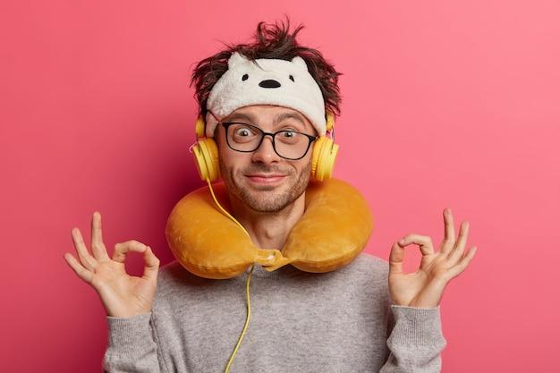 Passageiro do sexo masculino usando travesseiro de viagem inflado no pescoço e uma máscara de olho fofa