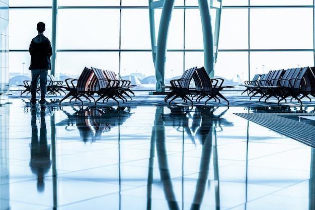 Passageiro em pé em um aeroporto no átrio, à espera de voo em silhueta