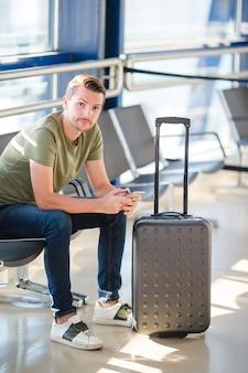 Passageiro, em, um, saguão aeroporto, esperando, para, vôo, aeronave, homem jovem, com, cellphone, em, aeroporto, esperando, para, aterragem