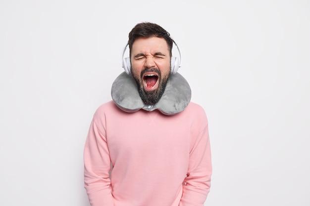Passageiro exausto e barbudo boceja com a boca bem aberta e mantém os olhos fechados ouve música com fones de ouvido enquanto viaja de carro ou avião vestido com um suéter casual