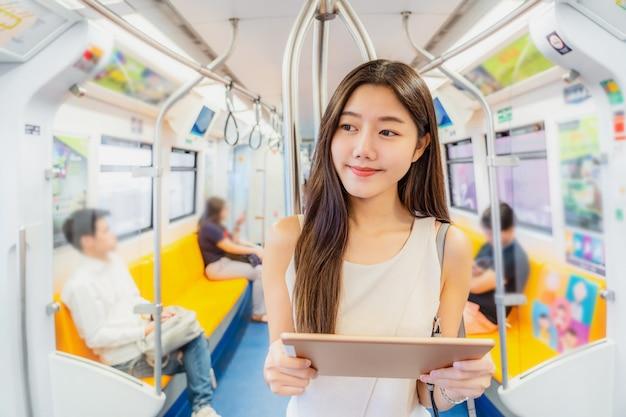 Passageiro jovem mulher asiática usando o leitor mutimedia através do tablet de tecnologia no trem do metrô
