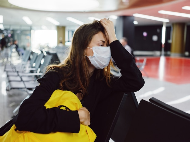 Passageiro usando máscara médica sentado na mochila amarela do aeroporto esperando