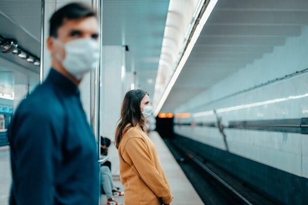 Passageiros com máscaras de proteção em pé na estação de metrô