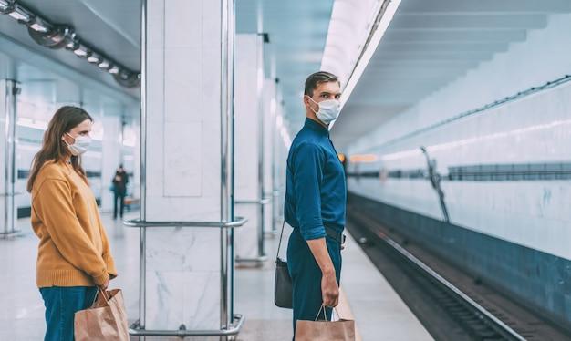 Passageiros com máscaras protetoras esperando o trem do metrô
