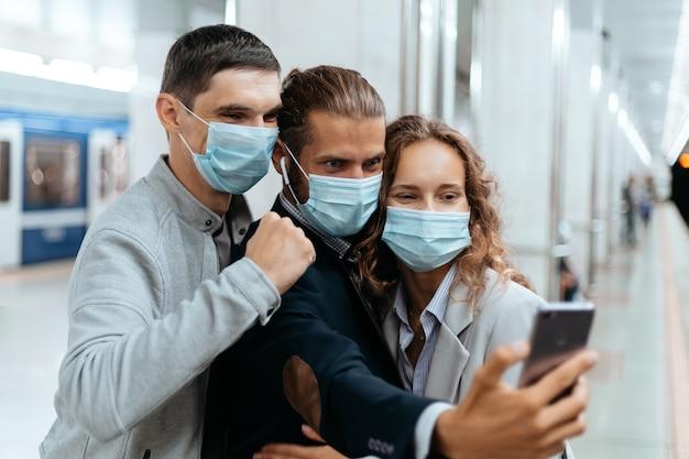 Passageiros com máscaras protetoras tirando selfies no metrô