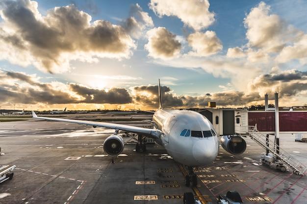 Passageiros de embarque de avião no aeroporto ao pôr do sol