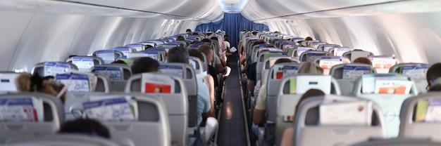 Passageiros sentados em assentos com vista traseira do avião