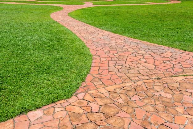 Passagem de pedra alaranjada com grama verde no parque. abstrato.