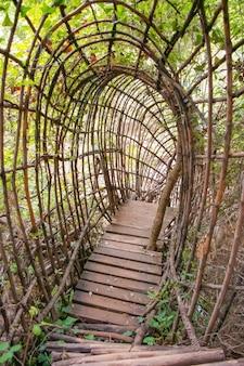 Passagem em forma de arco de bambu sobre um rio em uma floresta densa. uma incrível ponte de bambu na selva