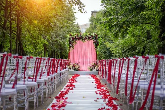 Passagem entre as cadeiras decoradas com pétalas de rosa leva ao arco do casamento