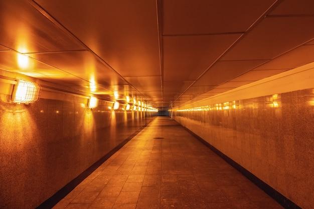 Passagem subterrânea vazia iluminada com luz amarela.