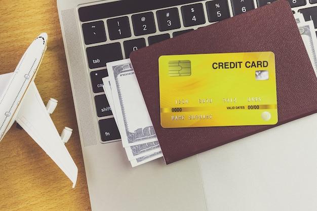 Passagens aéreas e passaportes perto de laptop e avião na mesa. conceito de reserva de bilhetes online
