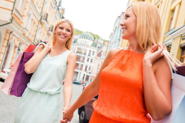 Passando bons momentos juntos. mulher jovem feliz e sua mãe carregando sacolas de compras e de mãos dadas enquanto caminhava pela rua
