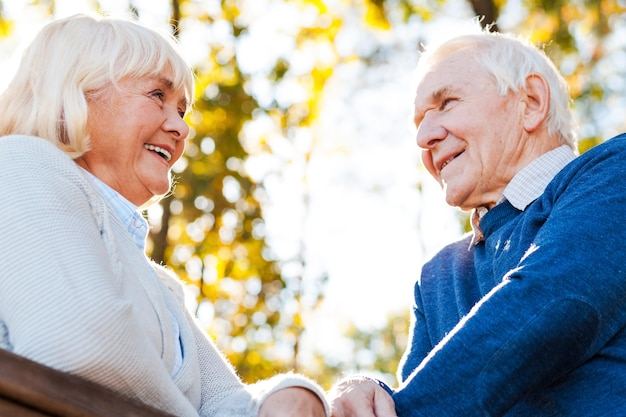 Passando bons momentos juntos. vista de baixo ângulo de um feliz casal de idosos olhando um para o outro e sorrindo ao ar livre