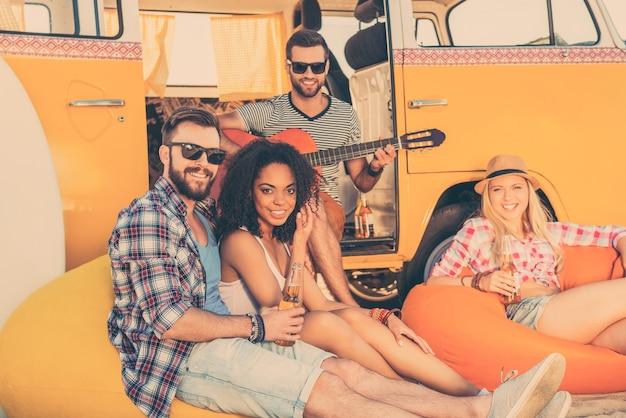 Passando o verão juntos. três jovens felizes sentados perto de sua minivan com garrafas de cerveja enquanto um homem tocando violão