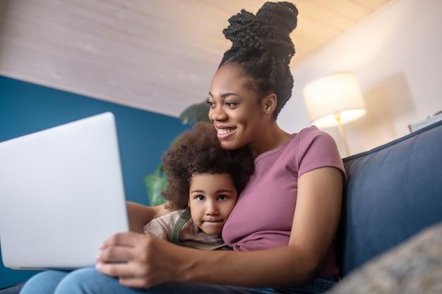Passando tempo. abraçou a mãe afro-americana e a garotinha encaracolada fofa olhando para o laptop em casa no sofá de bom humor