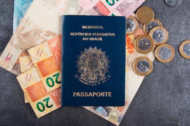 Passaporte brasileiro com notas e moedas reais.