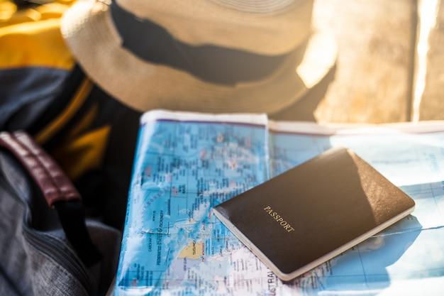 Passaporte colocado no mapa com um chapéu e bolsos laterais na estação de trem