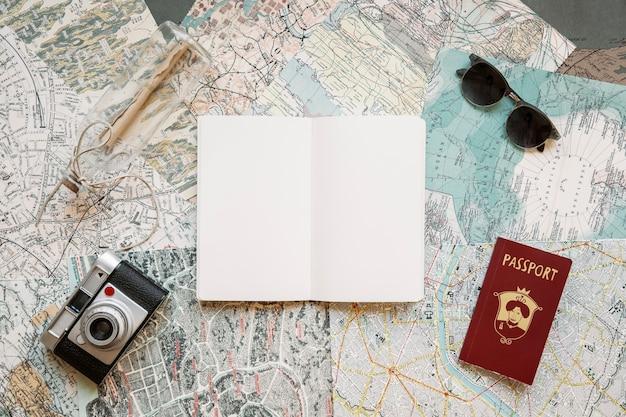 Passaporte com câmera e bloco de notas em mapas