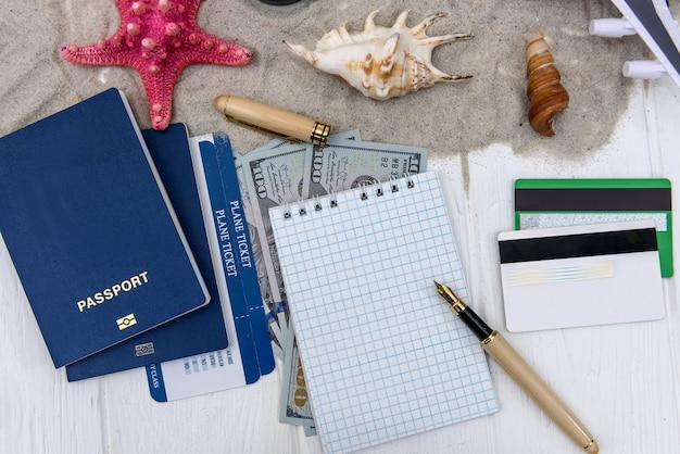 Passaporte com dólares, cartões de crédito, bloco de notas e caneta