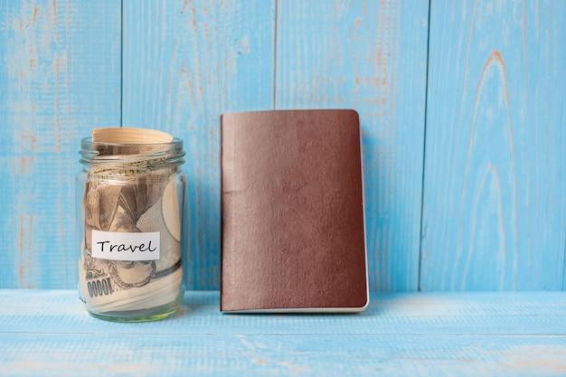 Passaporte com frasco de vidro de notas de dinheiro em madeira azul