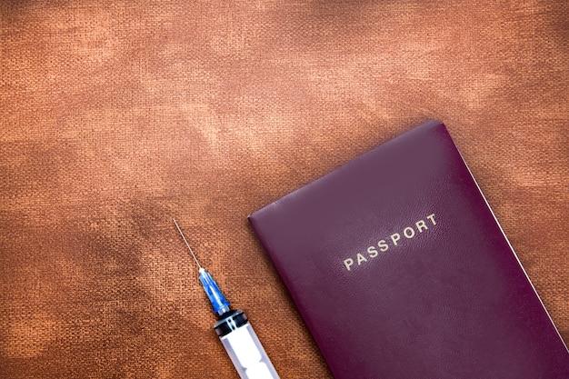 Passaporte com seringa para vírus de vacinação em parede de couro marrom com conceito de espaço de cópia