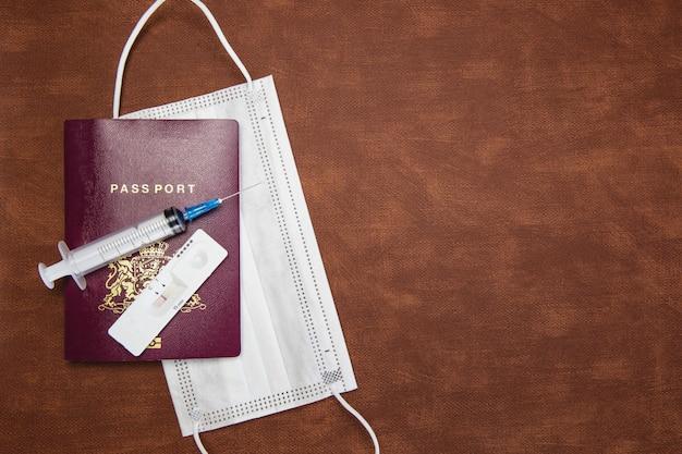 Passaporte de conceito de viagem e bloqueio cobiçoso com teste rápido negativo e seringa para exigência