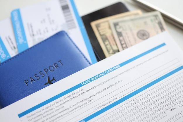 Passaporte de seguro médico de viagem e dinheiro na mesa escolha do conceito de seguro de viagem