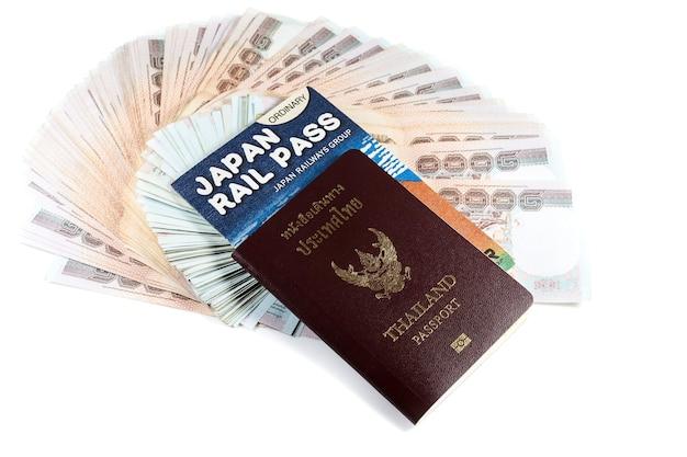 Passaporte, dinheiro e passagem de trem em fundo branco.
