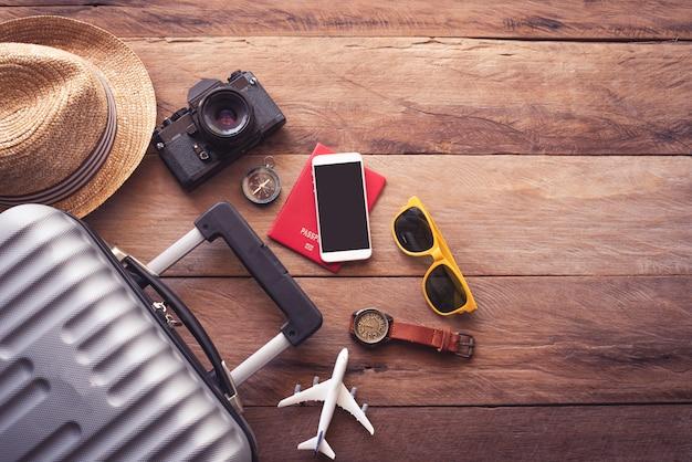 Passaporte do viajante de vestuário, carteira, óculos, dispositivos de telefone inteligente, sobre um piso de madeira na bagagem pronta para viajar.