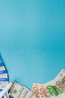 Passaporte, dólares e euros, passagem aérea e aérea sobre um fundo azul. conceito de viagens, cópia espaço