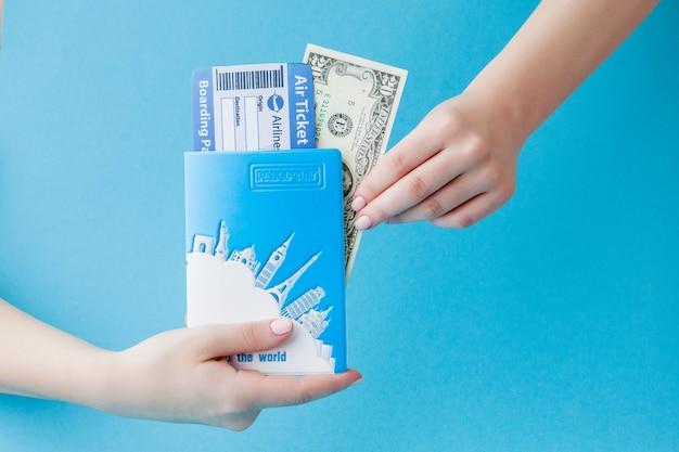 Passaporte, dólares e passagem aérea na mão da mulher no azul