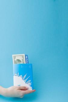 Passaporte, dólares e passagem aérea na mão da mulher, sobre um fundo azul. conceito de viagens, cópia espaço