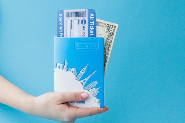 Passaporte, dólares e passagem aérea na mão da mulher