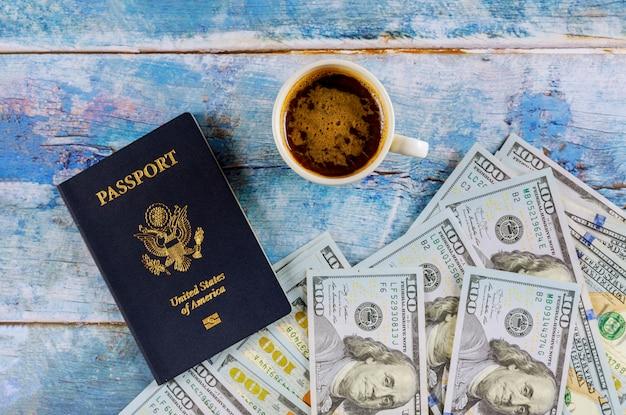 Passaporte dos eua com nota de dólar e xícara de café na mesa de madeira.