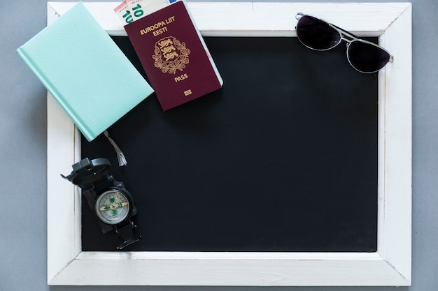 Passaporte e material turistico no quadro-negro