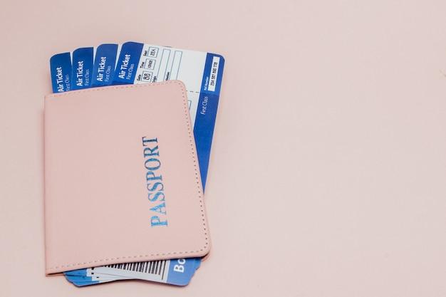 Passaporte e passagem aérea em um rosa.