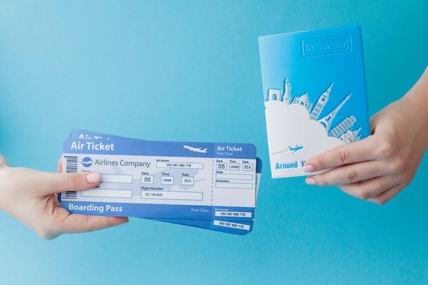 Passaporte e passagem aérea na mão da mulher, sobre um fundo azul. conceito de viagens, cópia espaço