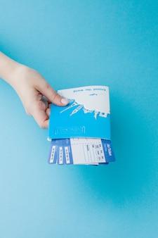 Passaporte e passagem aérea na mão de uma mulher em um azul