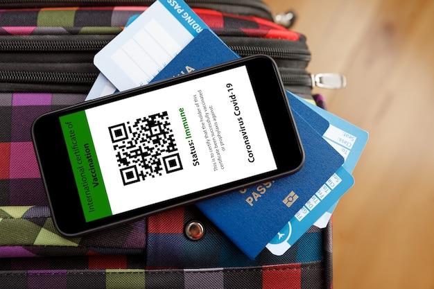 Passaporte e smartphone com digital do certificado de vacinação contra a doença de covid-19.