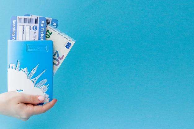 Passaporte, euro e passagem aérea na mão da mulher no azul