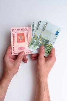 Passaporte internacional russo com euro na mão do homem