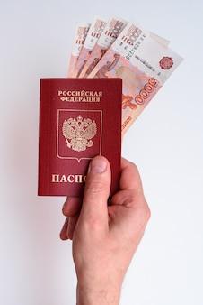 Passaporte internacional russo com rublos na mão do homem