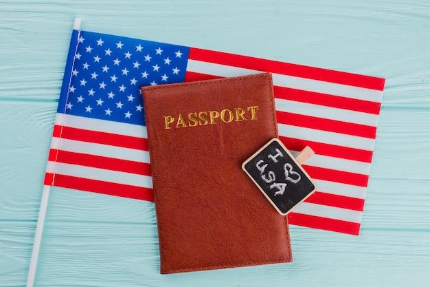 Passaporte liso leigo na pequena bandeira dos eua. eu amo os eua no pequeno quadro-negro. fundo azul claro.