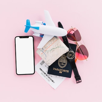 Passaporte; mapa; bilhetes; avião de brinquedo; relógio de pulso; telefone celular e óculos escuros no fundo rosa
