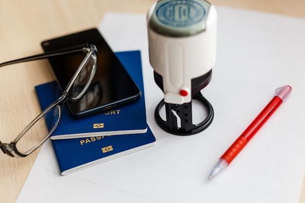 Passaporte no cartão de declaração com óculos e caneta