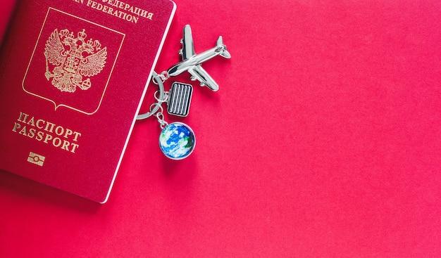 Passaporte para voos internacionais, avião de brinquedo, globo e bagagem de mão sobre fundo vermelho