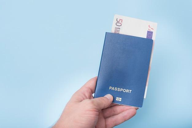 Passaporte vazio azul e dinheiro em euros na mão do homem. conceito de viagens. azul