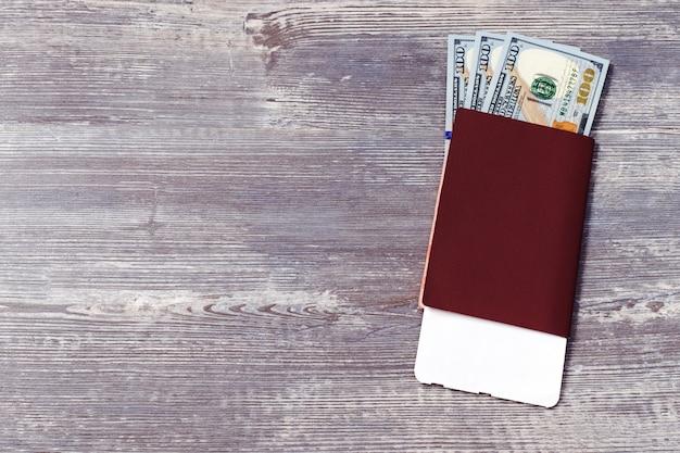 Passaporte vermelho com dinheiro e cartão de embarque para o conceito de viagens.